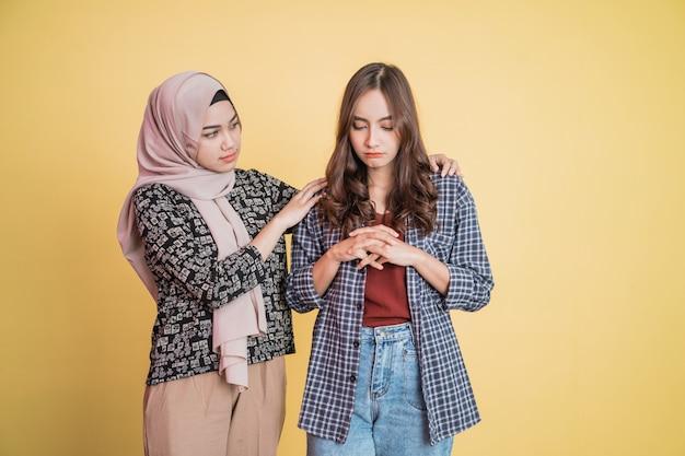 Uma triste menina asiática e uma menina velada aconselham com copyspace