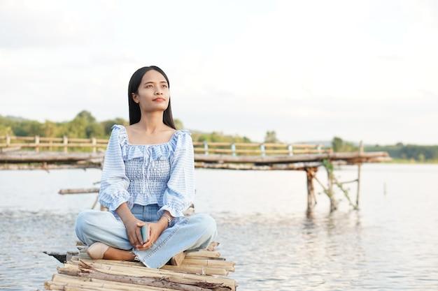 Uma turista asiática se senta em uma ponte de bambu para chegar ao mirante