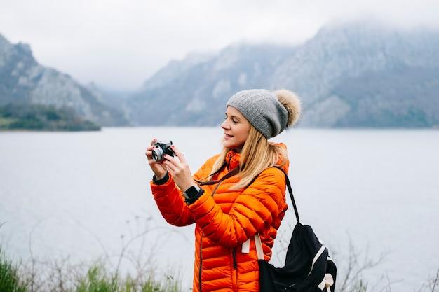 Uma turista loira linda, com um chapéu de lã, mochila e casaco laranja, usa a câmera em uma paisagem com lago e montanhas ao fundo