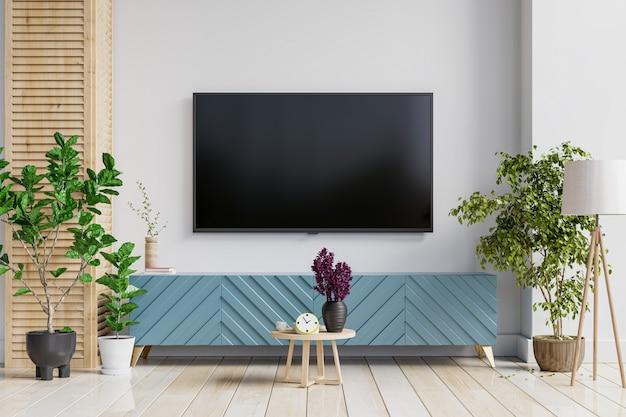 Uma tv na parede montada em um armário em uma sala de estar com uma parede branca