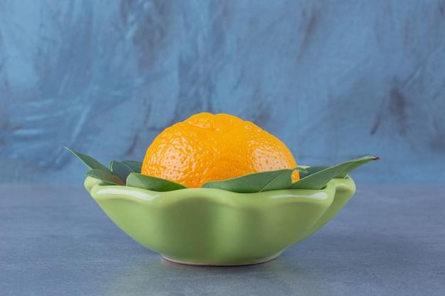 Uma única laranja com folhas em uma mesa de mármore bowlon.