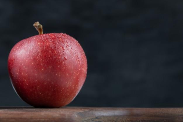 Uma única maçã vermelha em uma bandeja de madeira