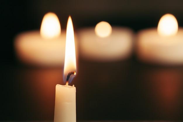 Uma única vela acesa isolada com fundo preto