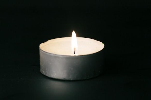 Uma única vela acesa isolada com preto