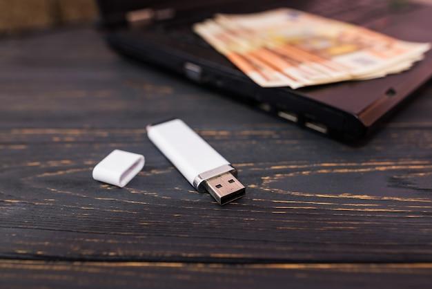 Uma unidade flash branca está perto de um laptop e notas de euro. fundo de madeira.