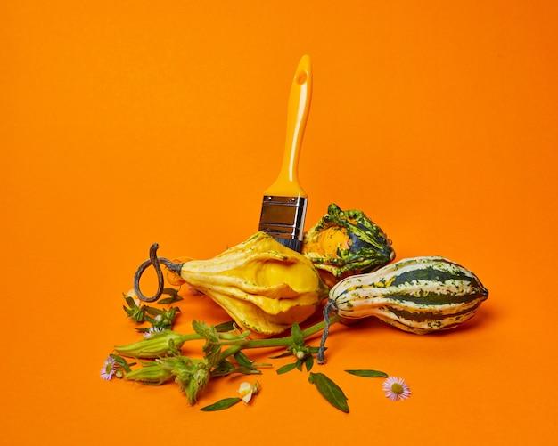Uma variedade de abóboras decorativas, um pincel, folhas verdes e flores em um fundo laranja. composição de outono