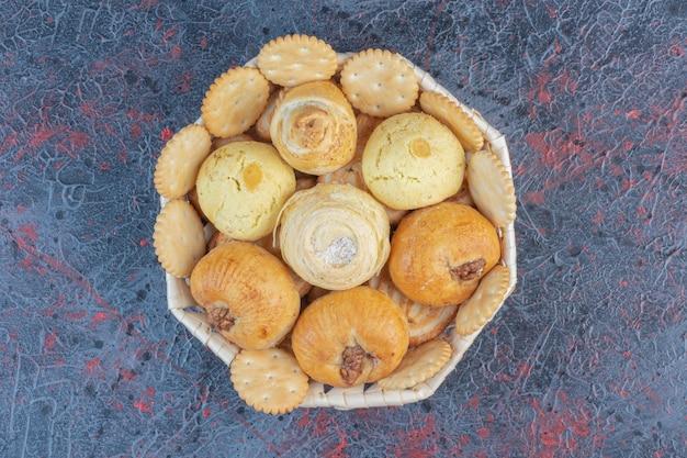 Uma variedade de biscoitos e bolachas em uma cesta na mesa abstrata.