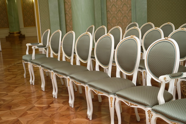 Uma variedade de cadeiras luxuosas e caras de design clássico para um evento especial.