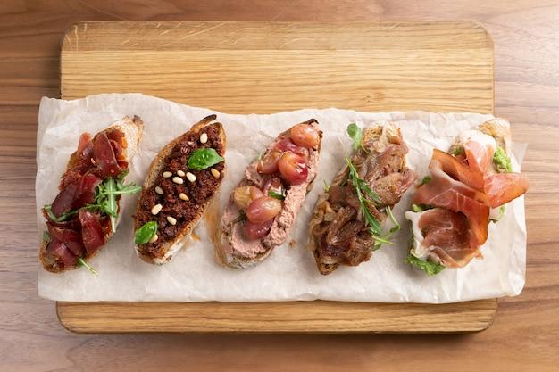 Uma variedade de cinco bruschettas diferentes com vegetais, carne, patê, bacon e ervas no pão escuro.