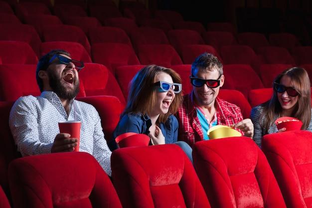 Uma variedade de emoções humanas de amigos segurando uma cola e pipoca no cinema.