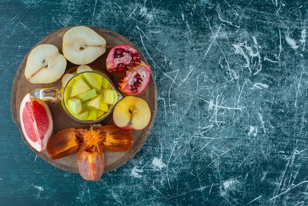 Uma variedade de fatias de frutas em uma placa com suco natural em uma garrafa de suco e maçã no fundo azul. foto de alta qualidade
