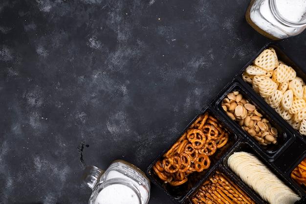 Uma variedade de lanches na caixa de cerveja em uma mesa preta concreta