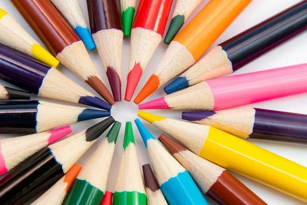 Uma variedade de lápis de cor em círculo, espiral sobre fundo branco. material escolar.