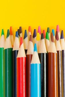 Uma variedade de lápis de cor sobre fundo amarelo.