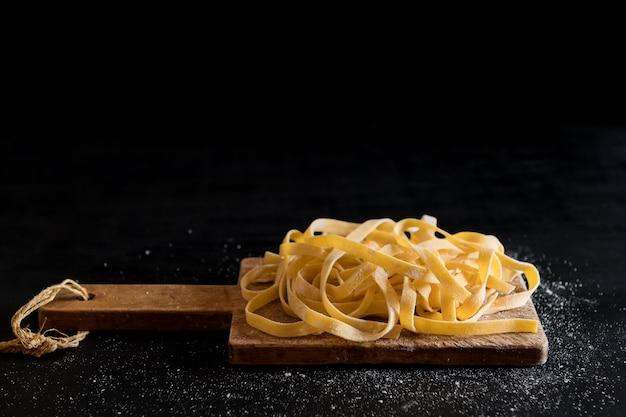 Uma variedade de massas tagliatelle cruas caseiras italianas em uma placa de corte com bela luz de fundo