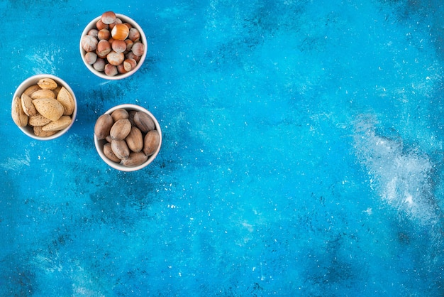 Uma variedade de nozes em tigelas, na mesa azul.