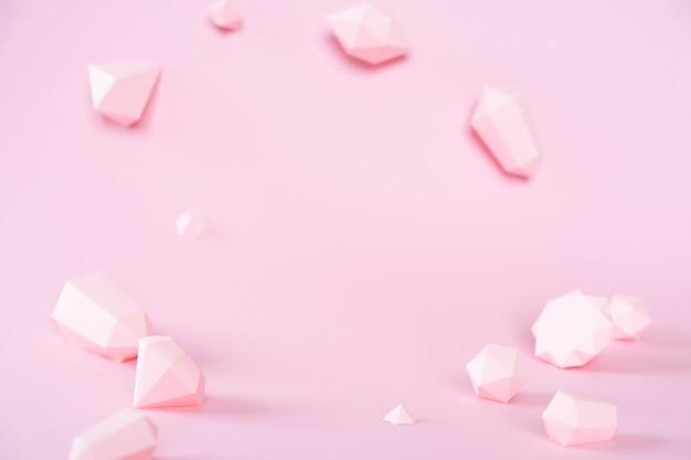 Uma variedade de pedras preciosas facetadas, feitas de papel em um fundo rosa.