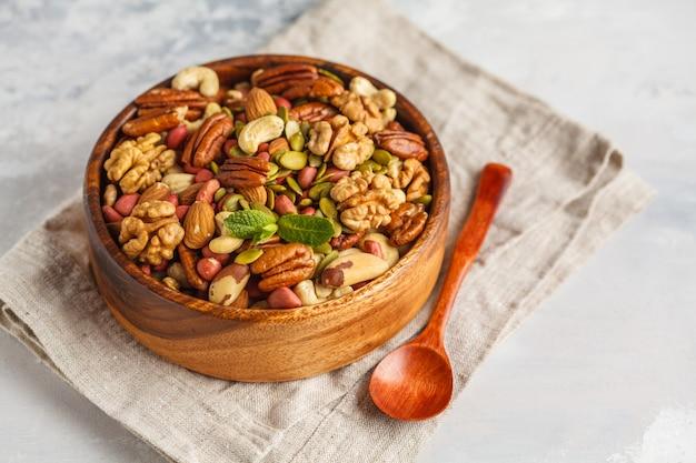 Uma variedade de porcas e sementes em uma bacia de madeira, fundo do alimento, conceito saudável do alimento do vegetariano. copie o espaço