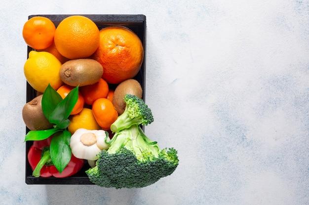 Uma variedade de produtos, legumes e frutas para manter a imunidade em uma caixa preta em um fundo branco. copie o espaço