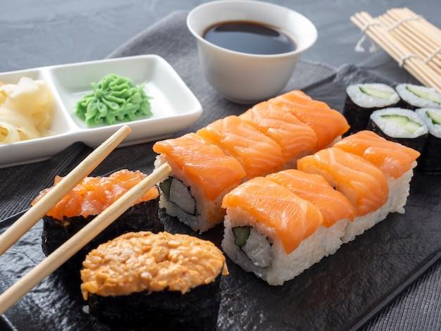 Uma variedade de rolos japoneses e sushi em um prato texturizado. vista lateral. palitos de bambu com gengibre e molho por perto.