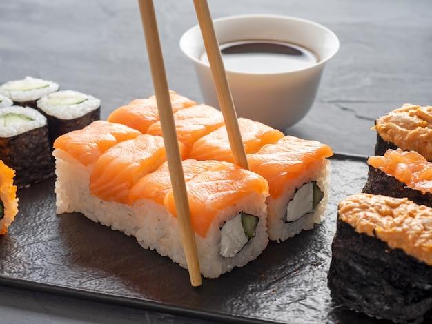 Uma variedade de rolos japoneses e sushi em uma placa preta texturizada. vista lateral. pauzinhos de bambu segurando um único rolo