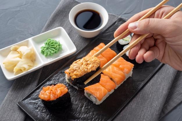 Uma variedade de rolos japoneses e sushi em uma placa preta texturizada. vista lateral. varas de bambu seguram um gunkan. fechar-se