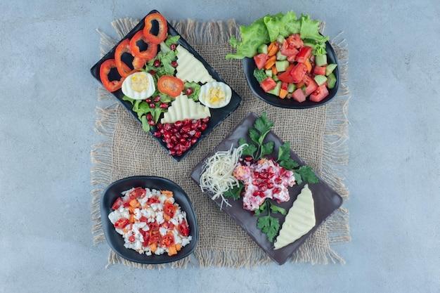 Uma variedade de saladas em travessas expostas em superfície de mármore