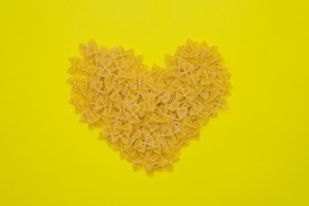Uma variedade de tipos e formas de massas italianas. os produtos de macarrão estão espalhados em forma de coração.