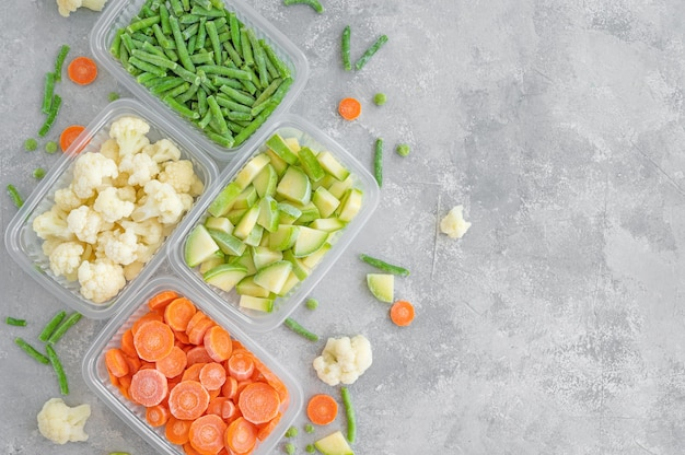 Uma variedade de vegetais congelados em recipientes de plástico em um fundo cinza de concreto.