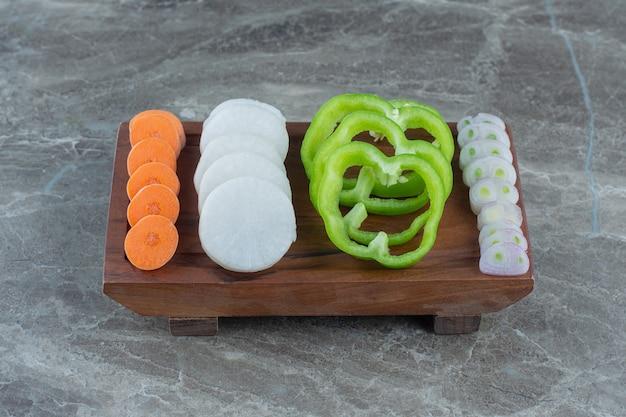 Uma variedade de vegetais fatiados, na mesa de mármore.
