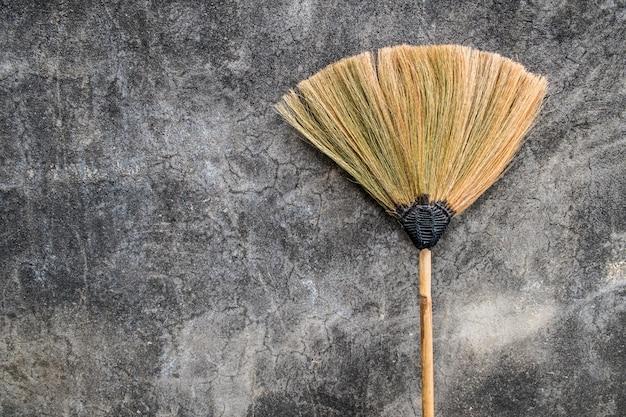 Uma vassoura de grama jazia contra a velha parede de cimento.