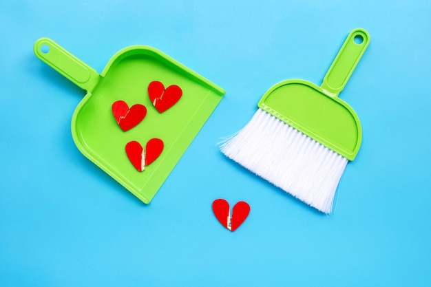 Uma vassoura e pá-de-lixo com corações partidos de madeira sobre fundo azul.