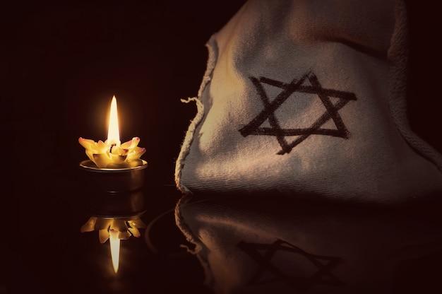 Uma vela acesa ao lado da estrela de david em um fundo preto. um símbolo de lembrança das vítimas do genocídio do judeu no terceiro reich na alemanha.