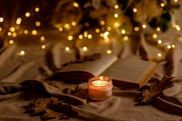 Uma vela acesa em uma mesa de madeira na frente de um livro a meio mastro. aprendendo. estudando a bíblia