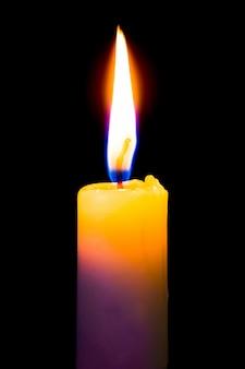 Uma vela amarela queima intensamente em um fundo preto e isolado