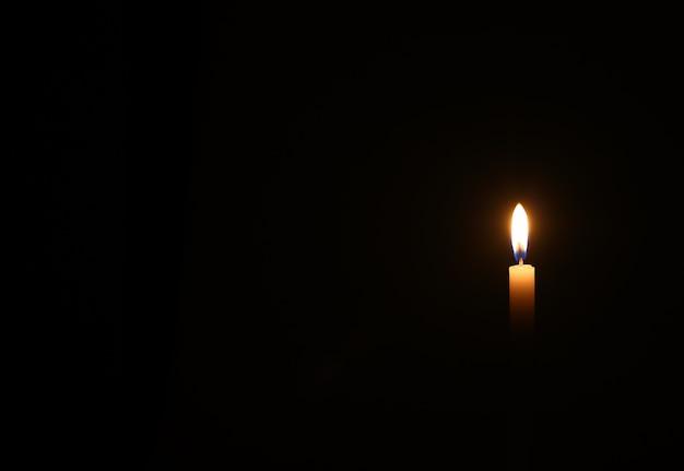 Uma vela amarela queima na parede preta