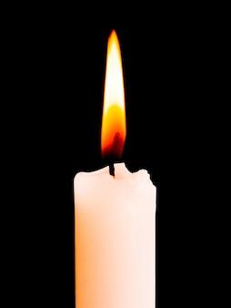 Uma vela branca queima intensamente em um fundo preto e isolado