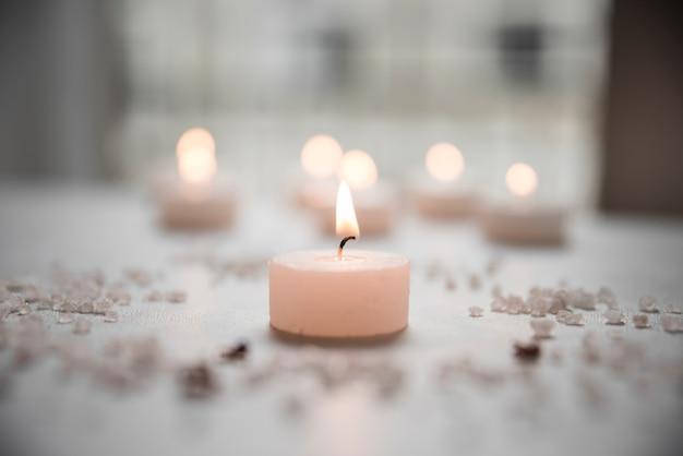 Uma vela iluminada e sal do mar no spa de beleza