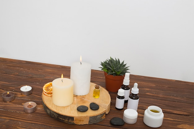 Uma vela iluminada; fatias cítricas secas; último; mel e garrafas de óleo essencial na planta de maconha sobre a mesa contra a parede