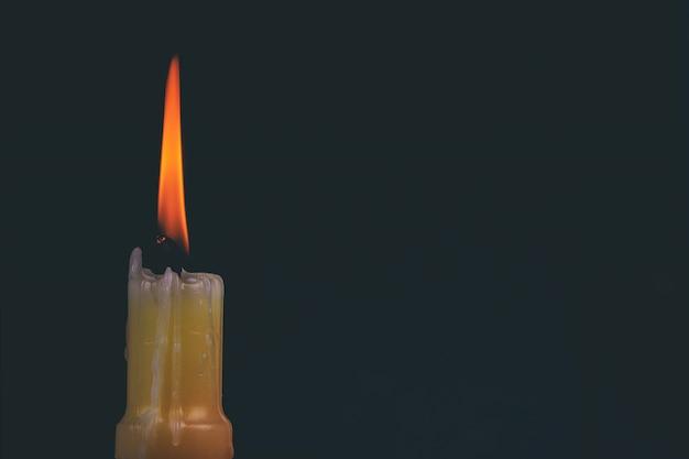 Uma vela memorial luz queimando brilhantemente no fundo preto