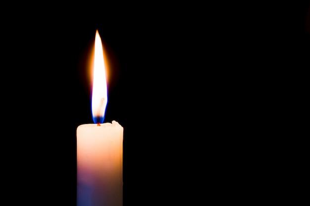 Uma vela queima intensamente em um fundo preto, isolado. espaço livre para texto