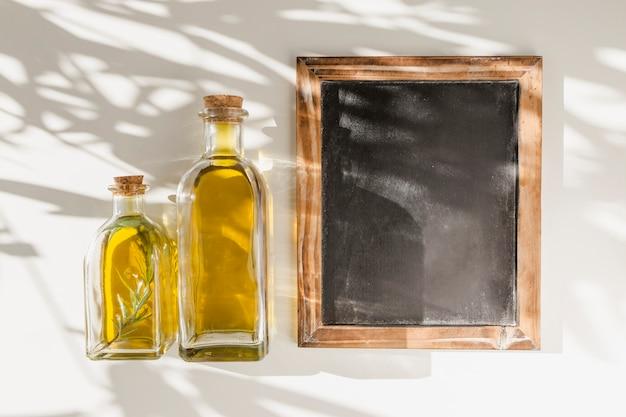 Uma velha ardósia de moldura de madeira em branco com duas garrafas de óleo contra a parede