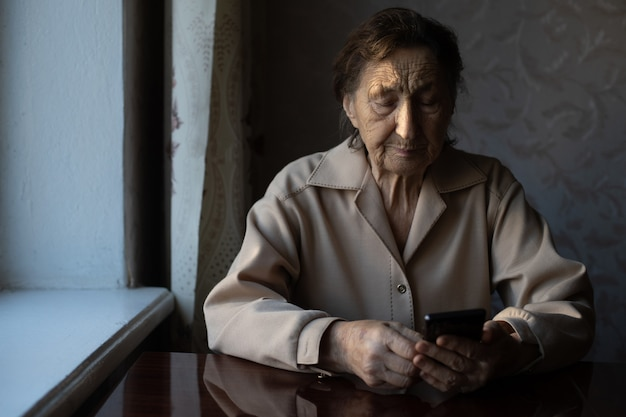 Uma velha avó caucasiana sênior com rugas profundas está sentada em casa, usa seu telefone inteligente na câmera frontal do braço estendido para uma videochamada.