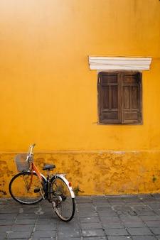 Uma velha bicicleta contra uma parede amarela com uma janela de madeira na cidade velha de hoi an. lugar para o rótulo.vietnam.