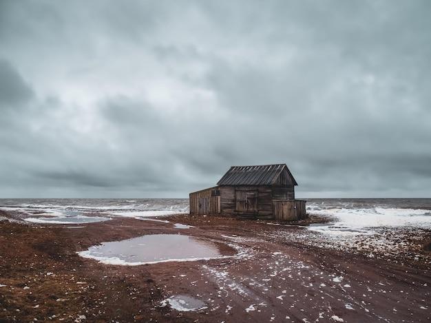 Uma velha cabana de pescador em ruínas em uma autêntica vila na costa do mar branco. a aldeia de umba, península de kola. rússia.
