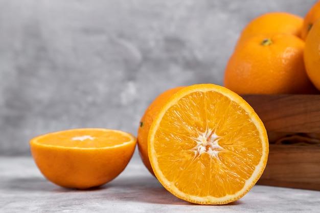 Uma velha caixa de madeira cheia de frutas inteiras e cortadas de laranja colocada em mármore