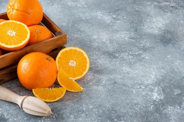 Uma velha caixa de madeira cheia de suculentas frutas laranja na mesa de pedra.