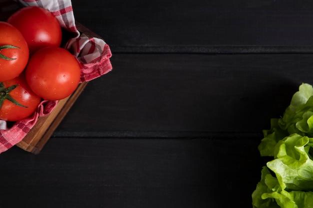 Uma velha caixa de madeira cheia de tomates vermelhos frescos e suculentos com salada de alface. foto de alta qualidade