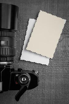 Uma velha câmera preta e duas fotos impressas na mesa. foco seletivo