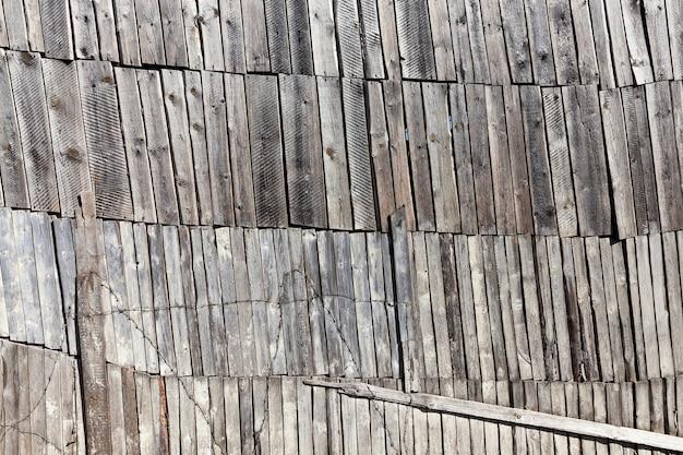 Uma velha casa de madeira feita de madeira e tábuas, uma grande e alta parede de vários níveis